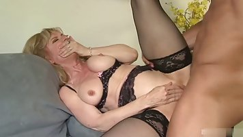 Sexy mature blonde in black, erotic lingerie is fucking a yo...