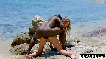 Fit blonde is having sex on the beach with a handsome, black...