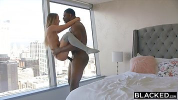 A muscled black dude is fucking a sexy, white chick while he...
