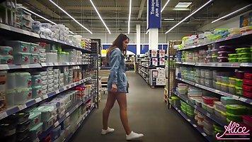 Девушка в джинсовом платье показывает на камеру в общественн...