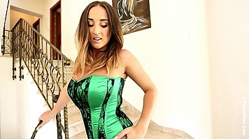 Curvaceous brunette in green satin corset with black lace is...