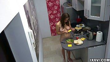 Брюнетка с большими сиськами прямо на кухне готовит завтрак ...