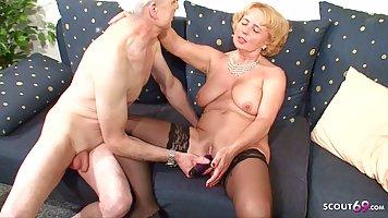 Зрелая женщина в чулках и старый дед на диване занимаются ре...
