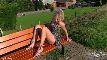Простая девушка в платье сидит на скамейке и потирает свою в...