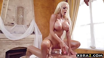 Gorgeous blonde masseuse with big, oiled tits is naked and e...