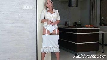 Зрелая дамочка сексуально раздевается на кухне